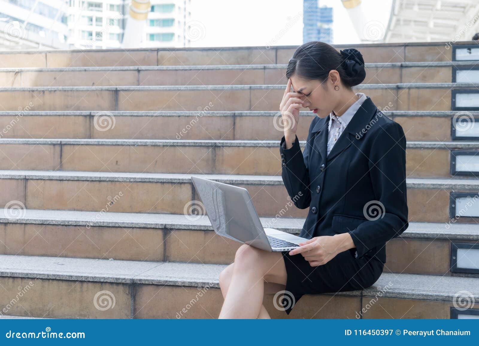 Οι επιχειρησιακές γυναίκες κάθονται στη σκάλα και εξέταση το lap-top τονίζει και χρησιμοποίησε το χέρι της για να κρατήσει το κεφ