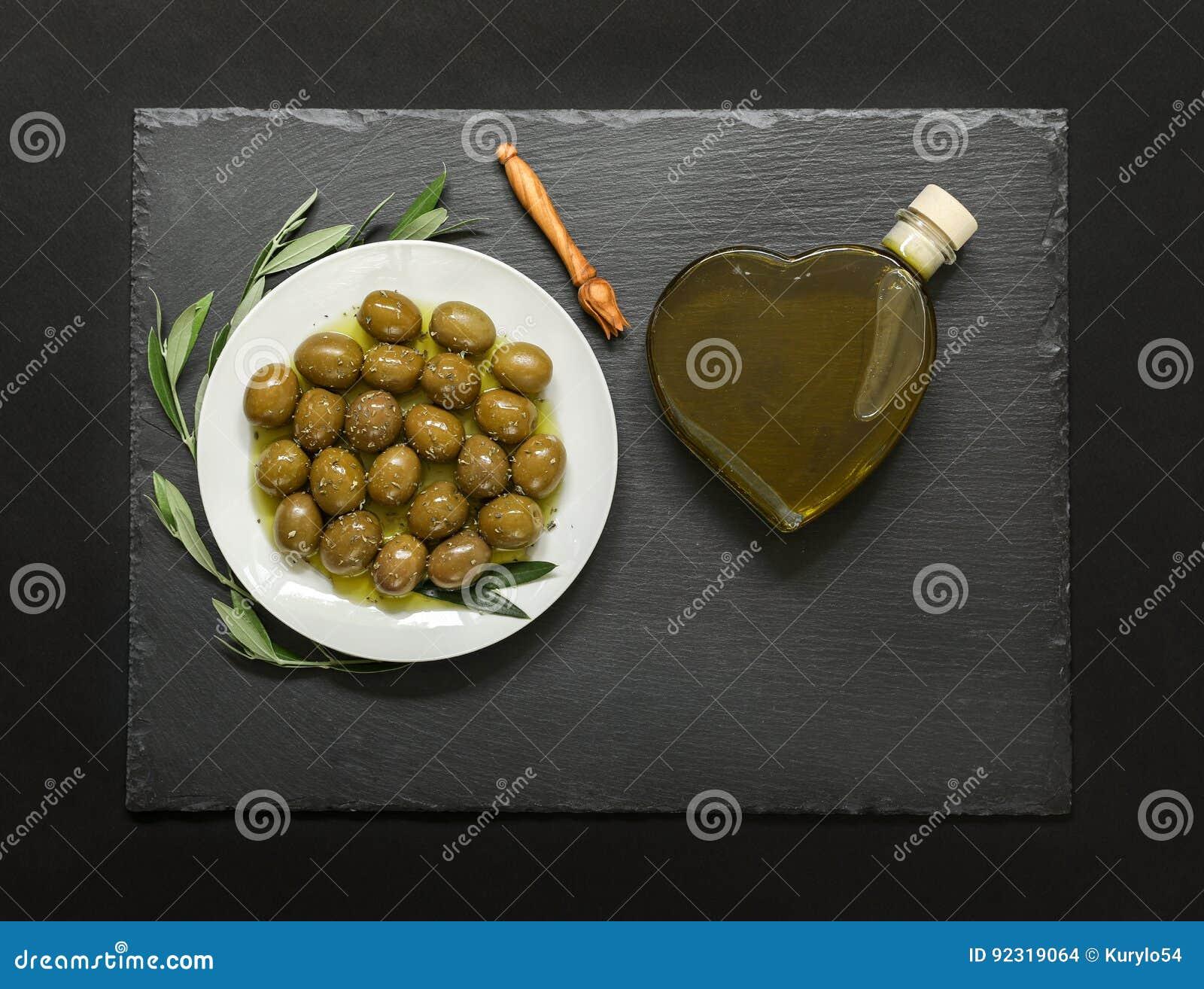 Οι επιλεγμένες ελιές σε ένα άσπρο πιάτο που διακοσμείται με τη φυσική ελιά διακλαδίζονται και το μπουκάλι καρδιών ελαιολάδου