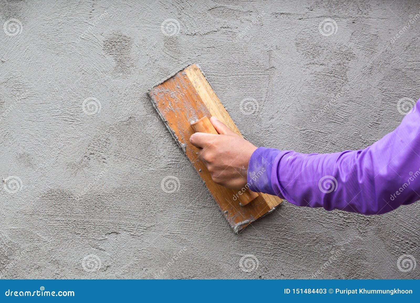 Οι εργαζόμενοι είναι επικονιασμένοι τοίχοι Γυψαδόρος χεριών στην εργασία Εφαρμογή του ασβεστοκονιάματος στον τοίχο