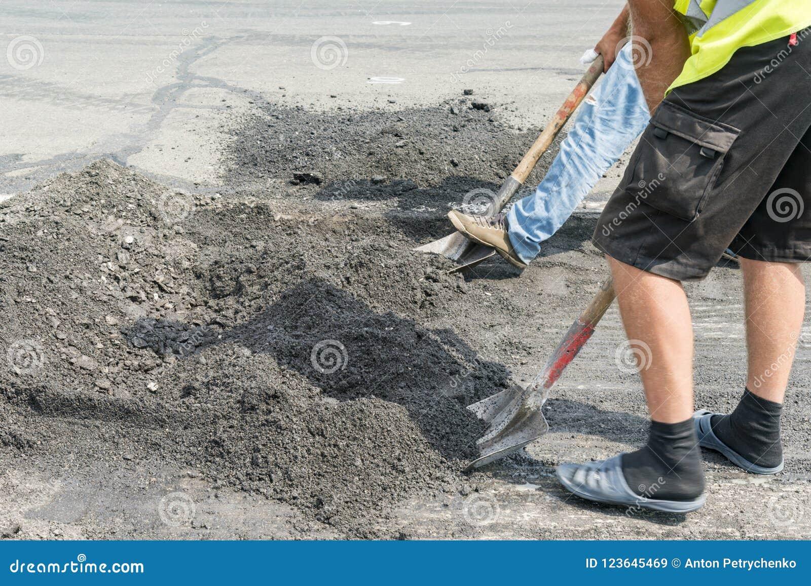 Οι εργαζόμενοι και τα μηχανήματα λειτουργούν το στρωμένο δρόμο με την άσφαλτο και το αμμοχάλικο, κατασκευή οδών για τη μεταφορά ε