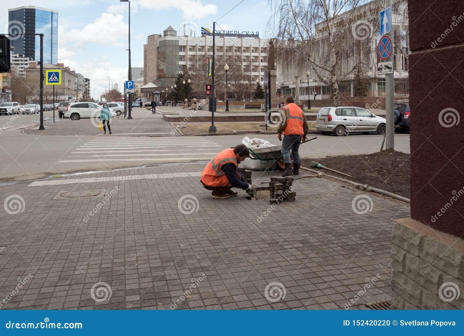 Οι εργαζόμενοι στις φωτεινές προστατευτικές φανέλλες επισκευάζουν τις πλάκες επίστρωσης μπροστά από ένα για τους πεζούς πέρασμα σ