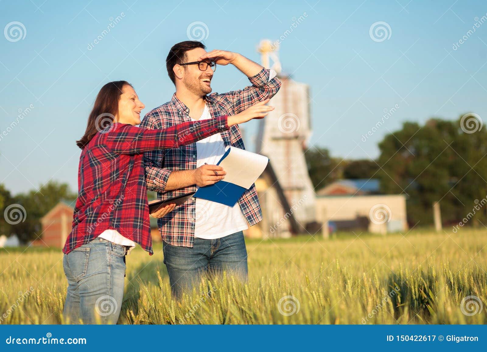 Οι ευτυχείς νέοι θηλυκοί και αρσενικοί γεωπόνοι ή οι αγρότες που επιθεωρούν τους τομείς σίτου ενώπιον της γυναίκας συγκομιδών δεί