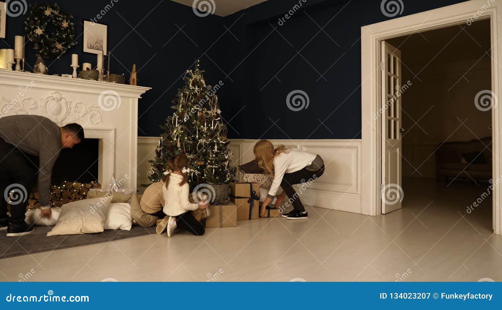 Οι ευτυχείς οικογενειακοί περίπατοι στο καθιστικό για να ελέγξουν παρουσιάζουν κάτω από το χριστουγεννιάτικο δέντρο