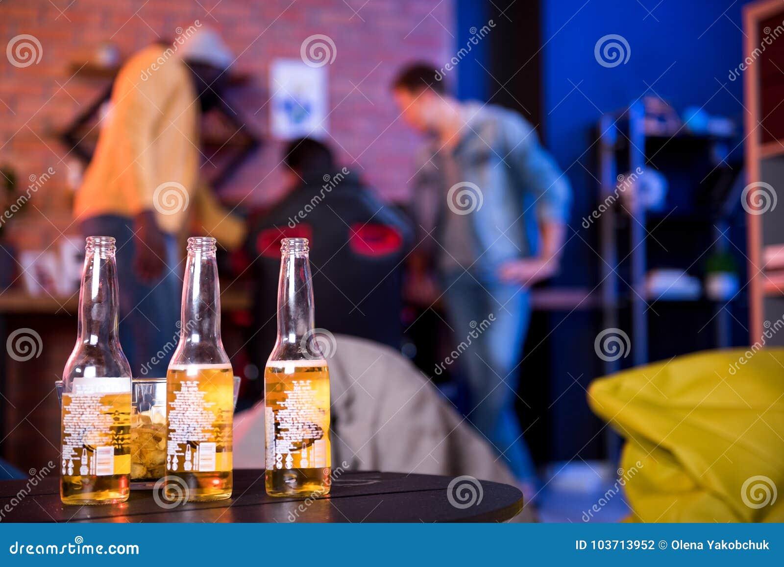 Οι ευχάριστοι φίλοι πίνουν την αγγλική μπύρα στο σπίτι