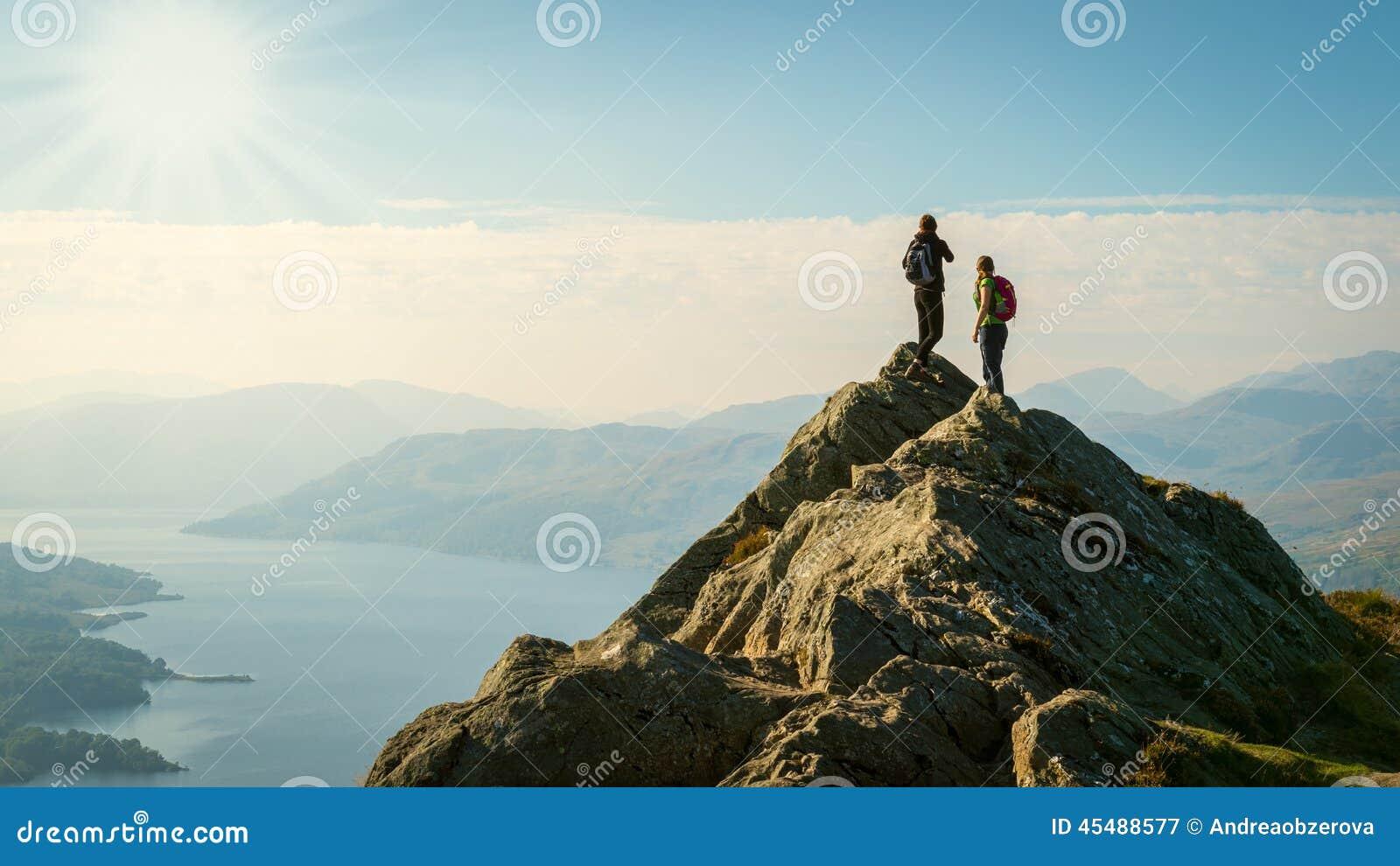 Οι θηλυκοί οδοιπόροι πάνω από το βουνό που απολαμβάνει την κοιλάδα βλέπουν
