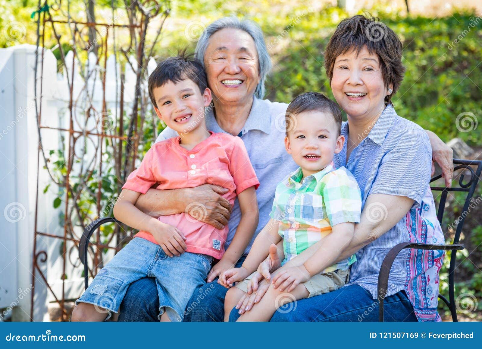 Οι κινεζικοί παππούδες και γιαγιάδες και τα μικτά παιδιά φυλών κάθονται στον πάγκο υπαίθρια
