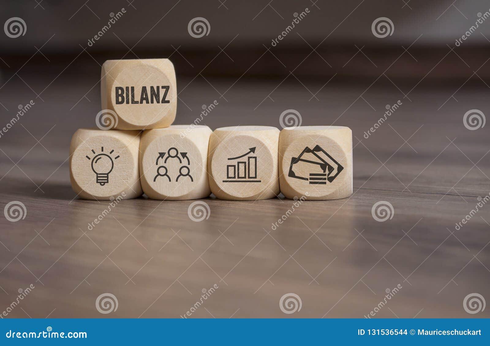 Οι κύβοι χωρίζουν σε τετράγωνα με τη γερμανική λέξη για την ισορροπία - Bilanz