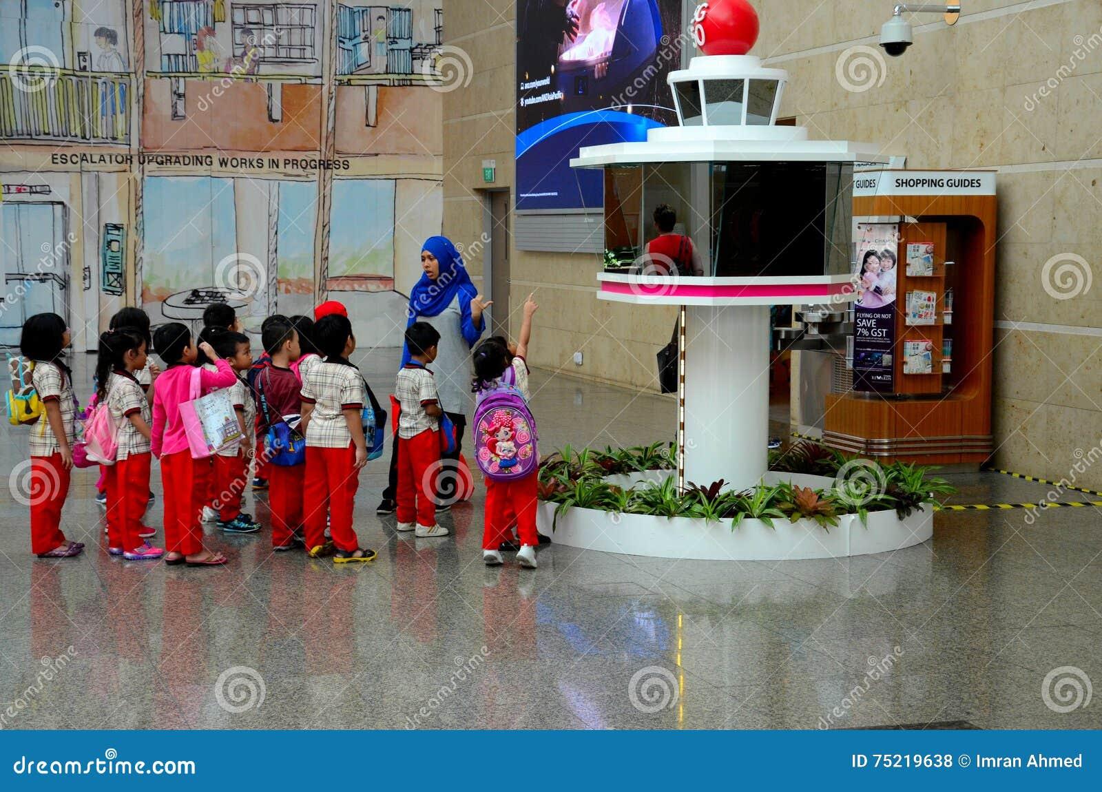 Οι μαθητές στον τομέα σκοντάφτουν με το δάσκαλο στον αερολιμένα Σιγκαπούρη Changi