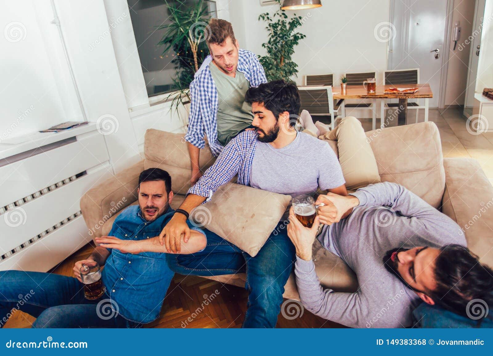 Οι μεθυσμένοι τύποι κοιμούνται αφότου θέτουν τα γεγονότα νύχτας στο πάτωμα και τον καναπέ σε διαφορετικό στο καθιστικό