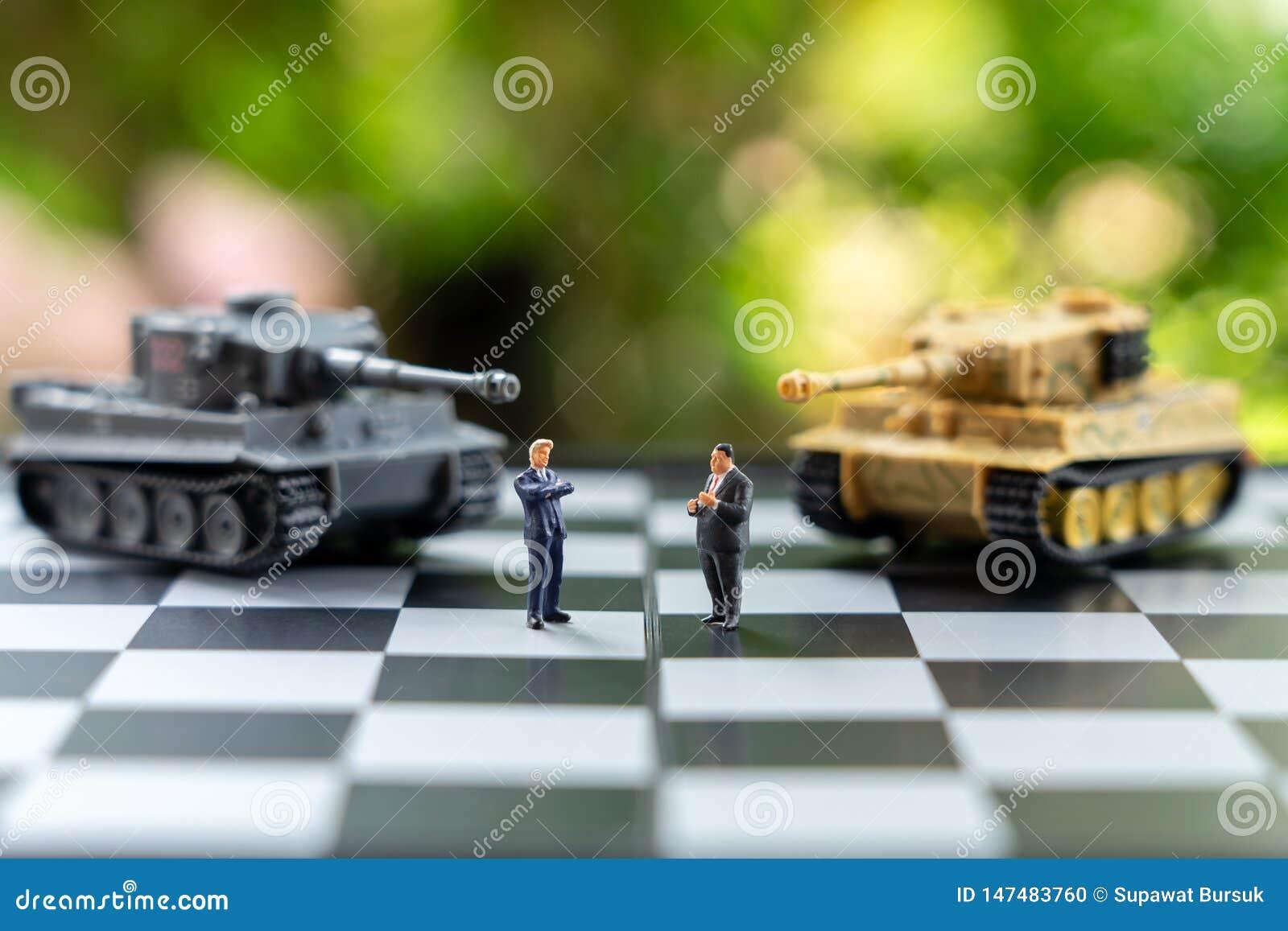 Οι μικροσκοπικοί επιχειρηματίες ανθρώπων που στέκονται σε μια σκακιέρα με μια δεξαμενή διαμορφώνουν σύμφωνα με την πίσω διαπραγμά