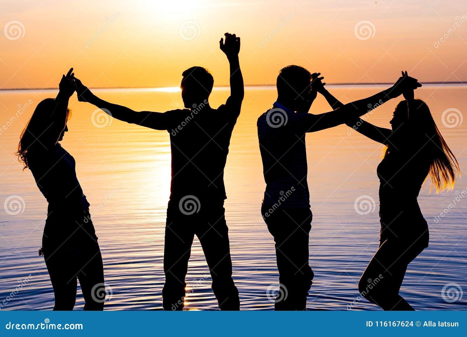 Οι νέοι, οι τύποι και τα κορίτσια είναι χορεύοντας ζεύγη στο ηλιοβασίλεμα backg