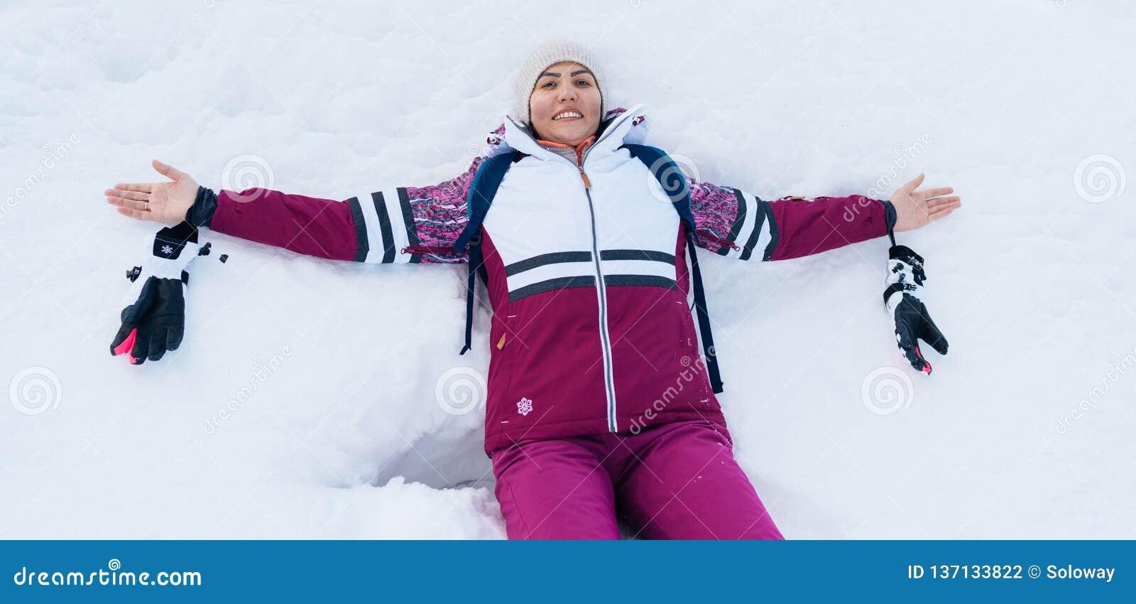 Οι νεολαίες που χαμογελούν θηλυκά στο άσπρο χιόνι άνοιξαν ευρέως τις αγκάλες της