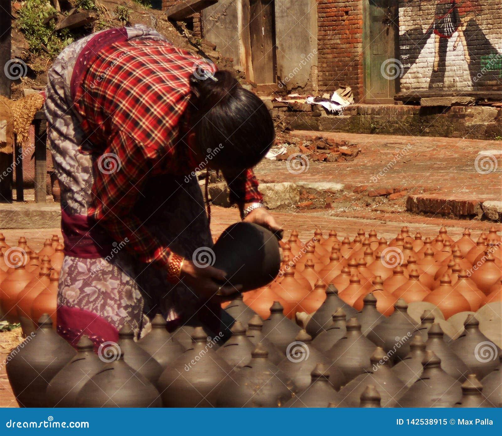 Οι νεπαλικοί λαοί διαμορφώνουν και στεγνώνουν τα δοχεία κεραμικής στο τετράγωνο αγγειοπλαστικής