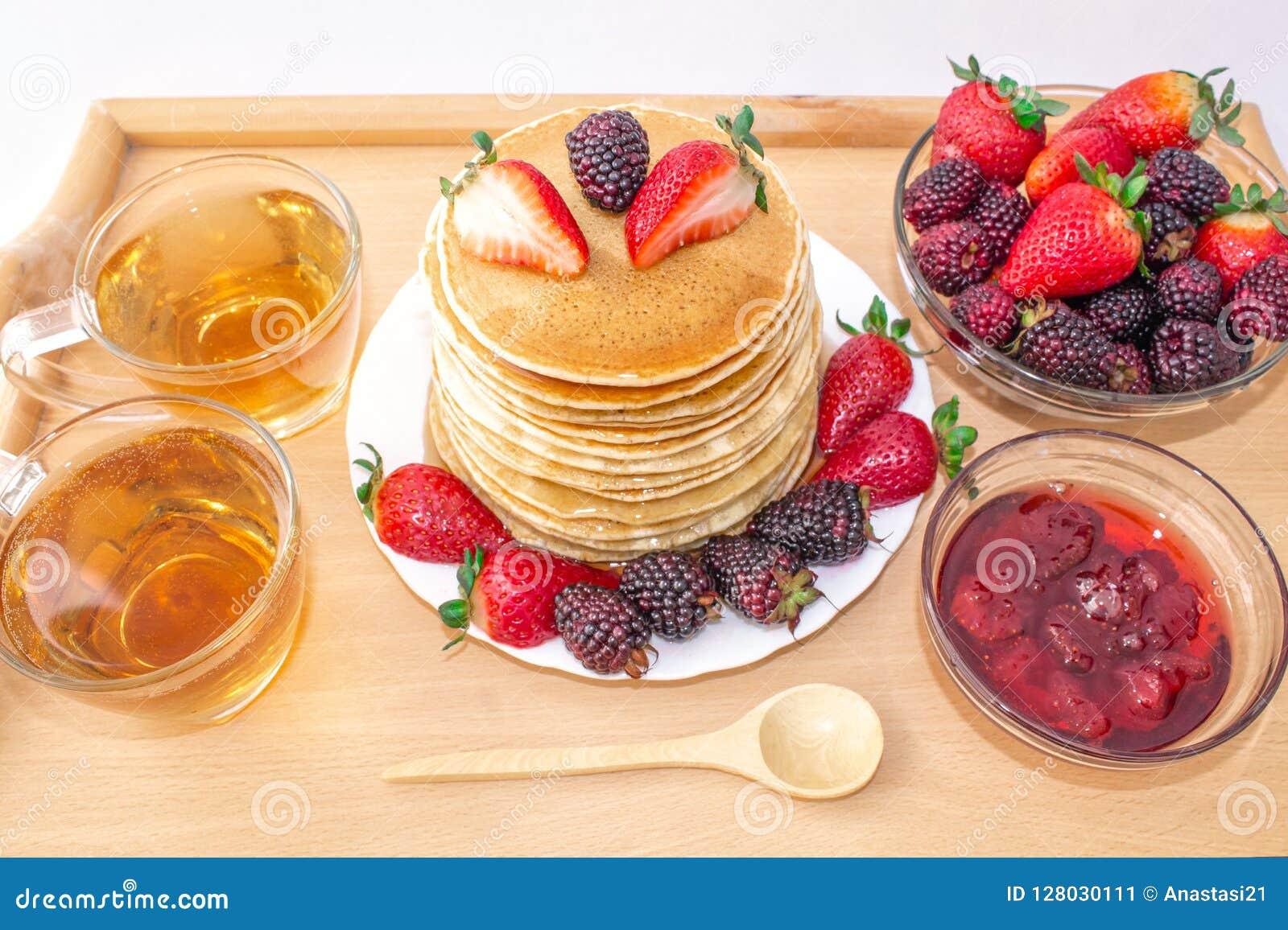 Οι νόστιμες τηγανίτες προγευμάτων με το mora φρούτων, φραουλών και βατόμουρων, έχυσαν το μέλι σιροπιού σε έναν ξύλινο δίσκο