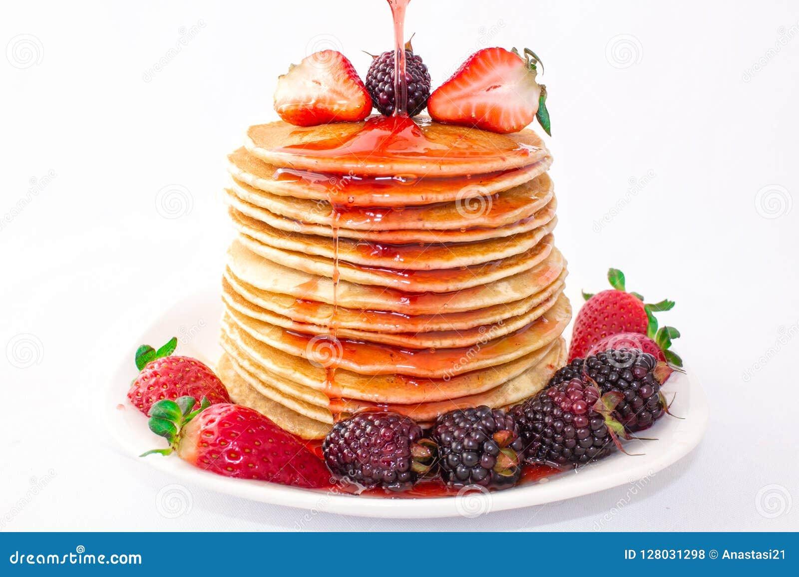 Οι νόστιμες τηγανίτες προγευμάτων με το mora φρούτων, φραουλών και βατόμουρων χύνονται με τη μαρμελάδα σιροπιού φραουλών Κινηματο