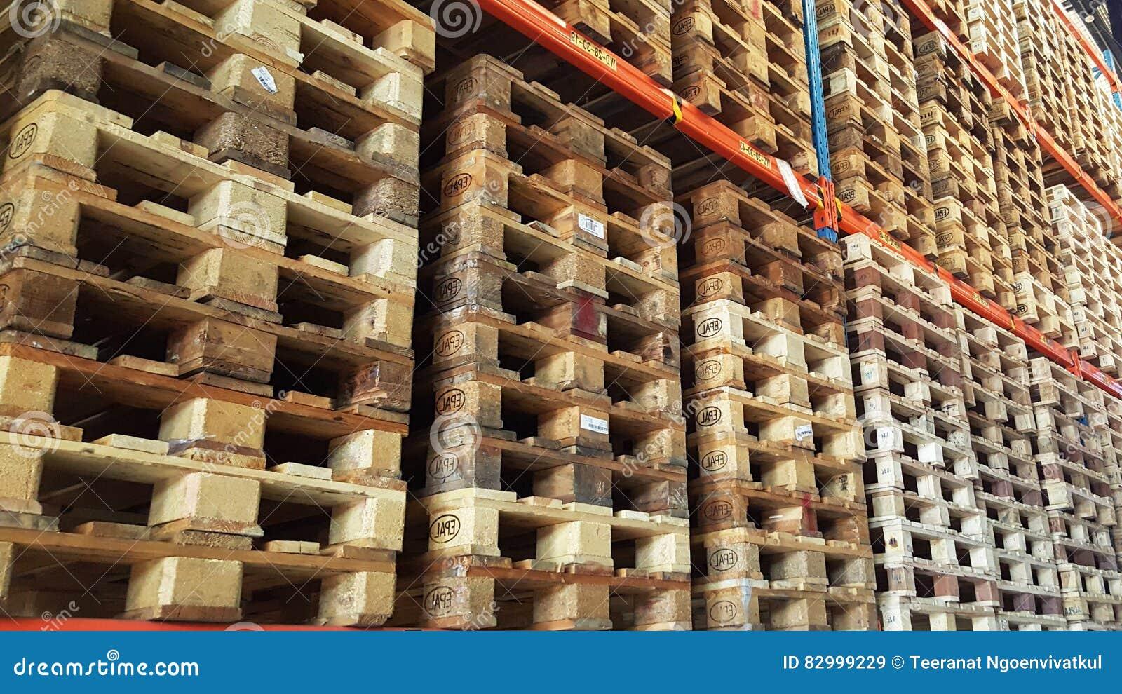 Οι ξύλινες παλέτες για τη διανομή και τη μεταφορά προϊόντων συσσωρεύονται στο ράφι της αποθήκης εμπορευμάτων