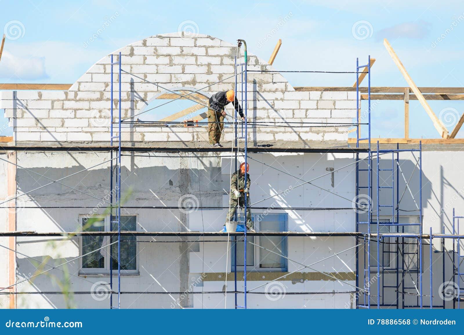 Οι οικοδόμοι εργαζομένων ανυψώνουν τα οικοδομικά υλικά στα υλικά σκαλωσιάς