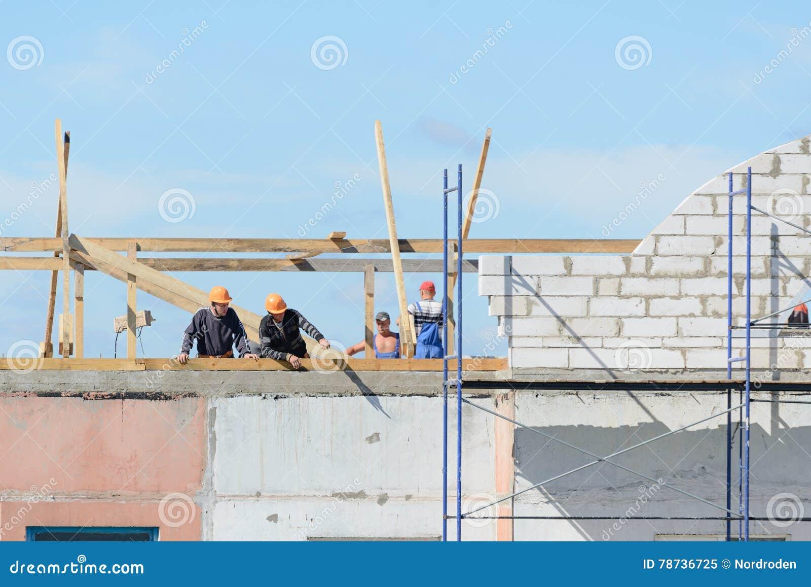 Οι οικοδόμοι εργαζομένων κάνουν την εγκατάσταση των υλικών σκαλωσιάς