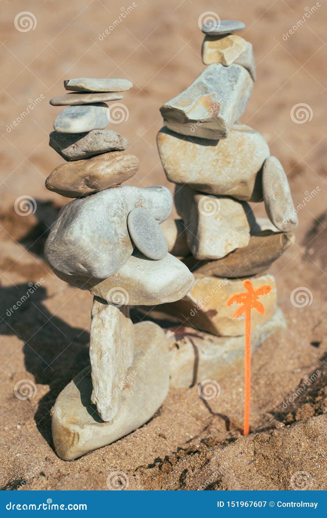 Οι πέτρες βρίσκονται στις πέτρες feng shui στην παραλία Δημιουργία μιας ισορροπίας στην άμμο