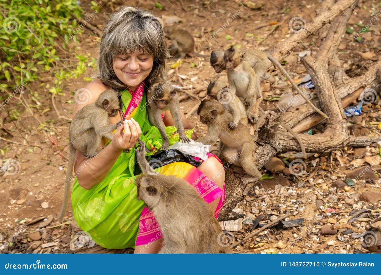 Οι πίθηκοι περιέβαλαν έναν ευτυχή τουρίστα που τους ταΐζει με τα φρούτα