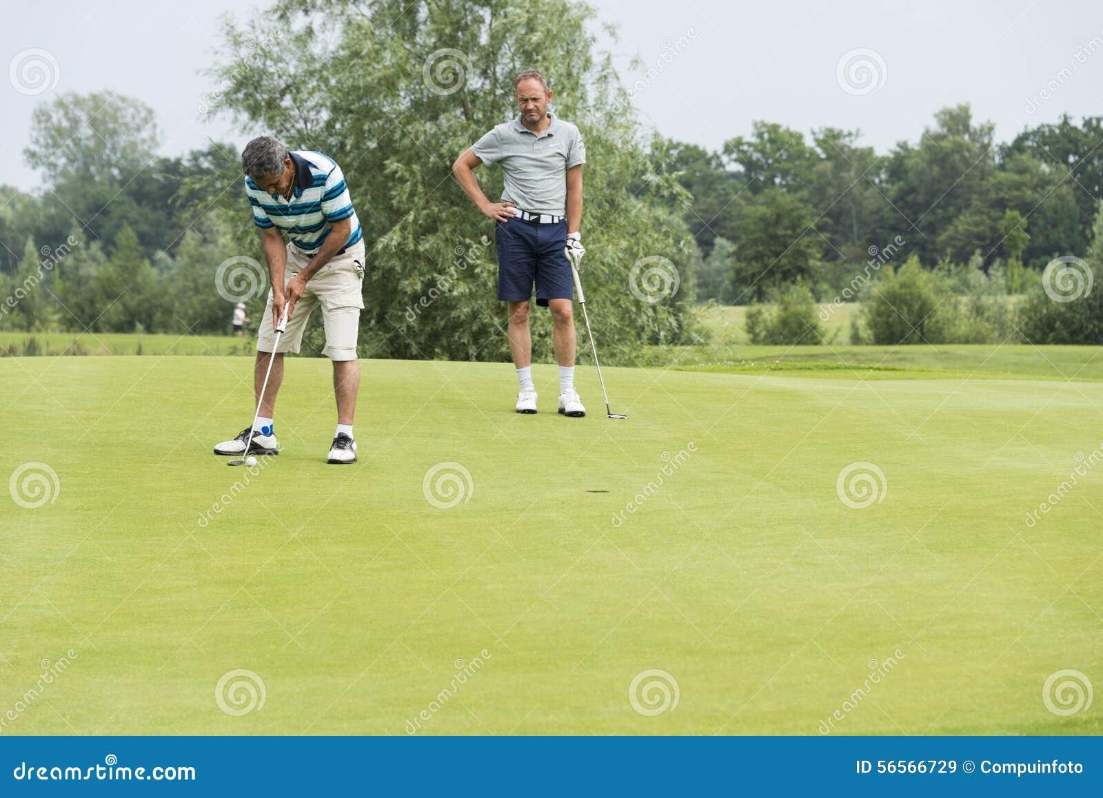 Download Οι παίκτες γκολφ παίζουν τη σφαίρα στο πράσινο Εκδοτική Στοκ Εικόνα - εικόνα από αρσενικό, εκδοτικός: 56566729