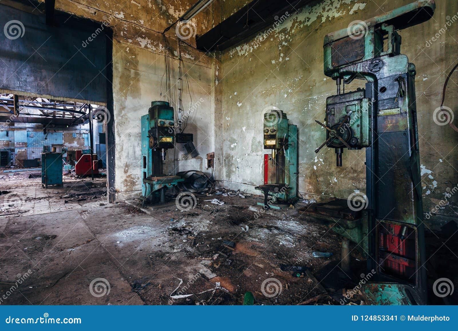 Οι παλαιές σκουριασμένες βιομηχανικές μηχανές διατρήσεων στο εγκαταλειμμένο εργαστήριο εργοστασίων μοιάζουν με τα ρομπότ