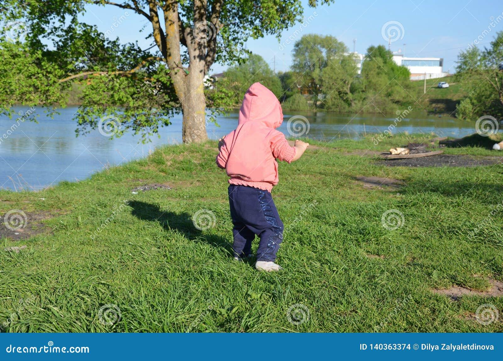 Το χαμογελώντας χαριτωμένο εύθυμο μικρό κορίτσι στέκεται στην πράσινη χλόη οι περίπατοι μικρών παιδιών κοριτσιών γύρω από τη λίμν