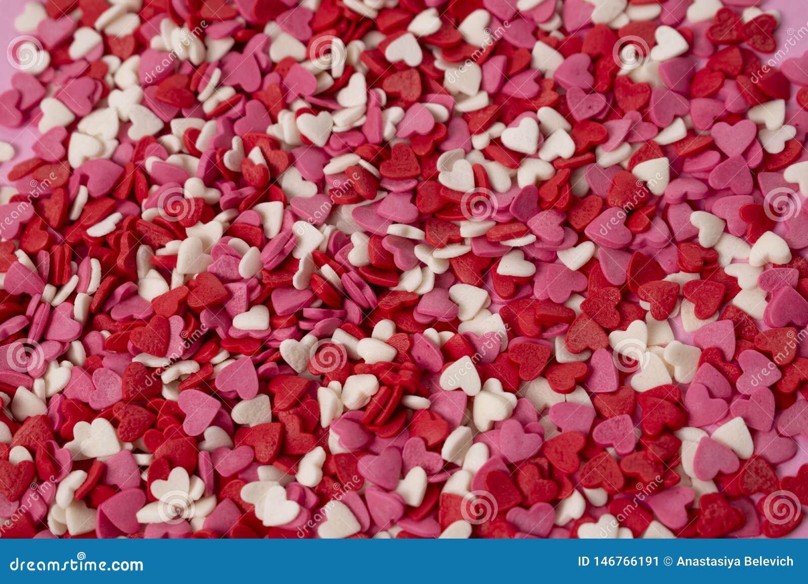 Οι πολύ μικρές καρδιά-διαμορφωμένες καραμέλες είναι διεσπαρμένες πέρα από το υπόβαθρο Πολλές μικρές φωτεινές καρδιές σε μεγάλη πο