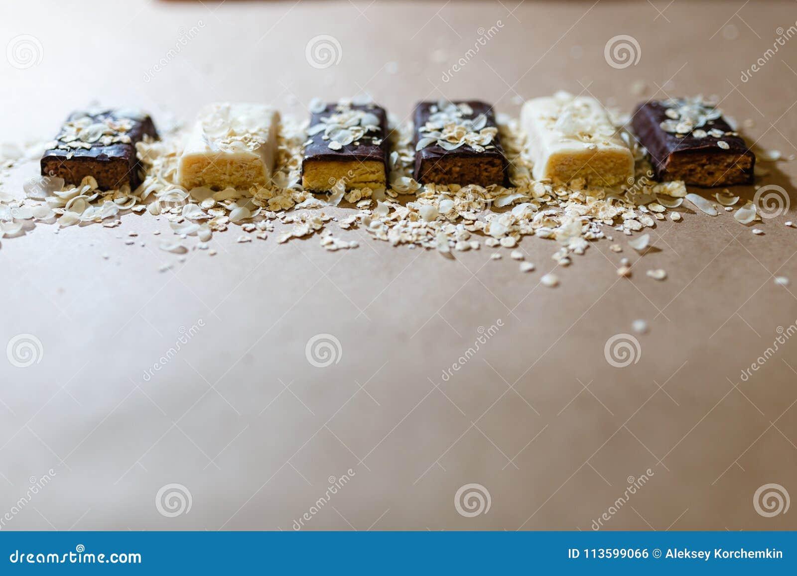 Οι πρωτεϊνικοί φραγμοί σοκολάτας πρόχειρων φαγητών με τις διαφορετικές γεύσεις στα πλαίσια ψεκάζουν τις νιφάδες ρυζιού σε χαρτί ψ