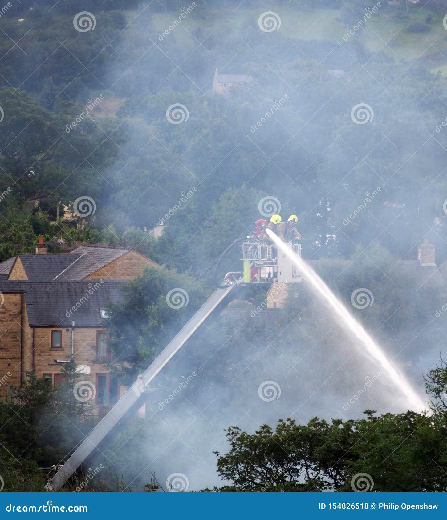 Οι πυροσβέστες σε μια ανυψωμένη πλατφόρμα που σβήνει την πυρκαγιά στον προηγούμενο clogs walkeys μύλο μέσα η γέφυρα