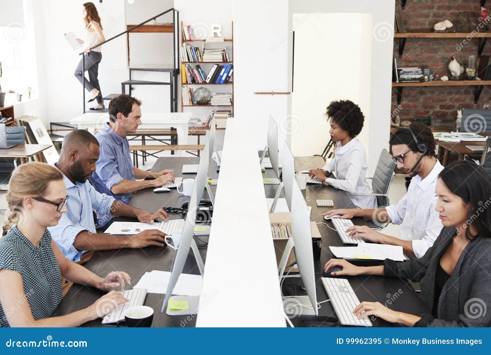 Οι συνάδελφοι κάθονται χρησιμοποιώντας τους υπολογιστές σε ένα πολυάσχολο ανοικτό γραφείο σχεδίων