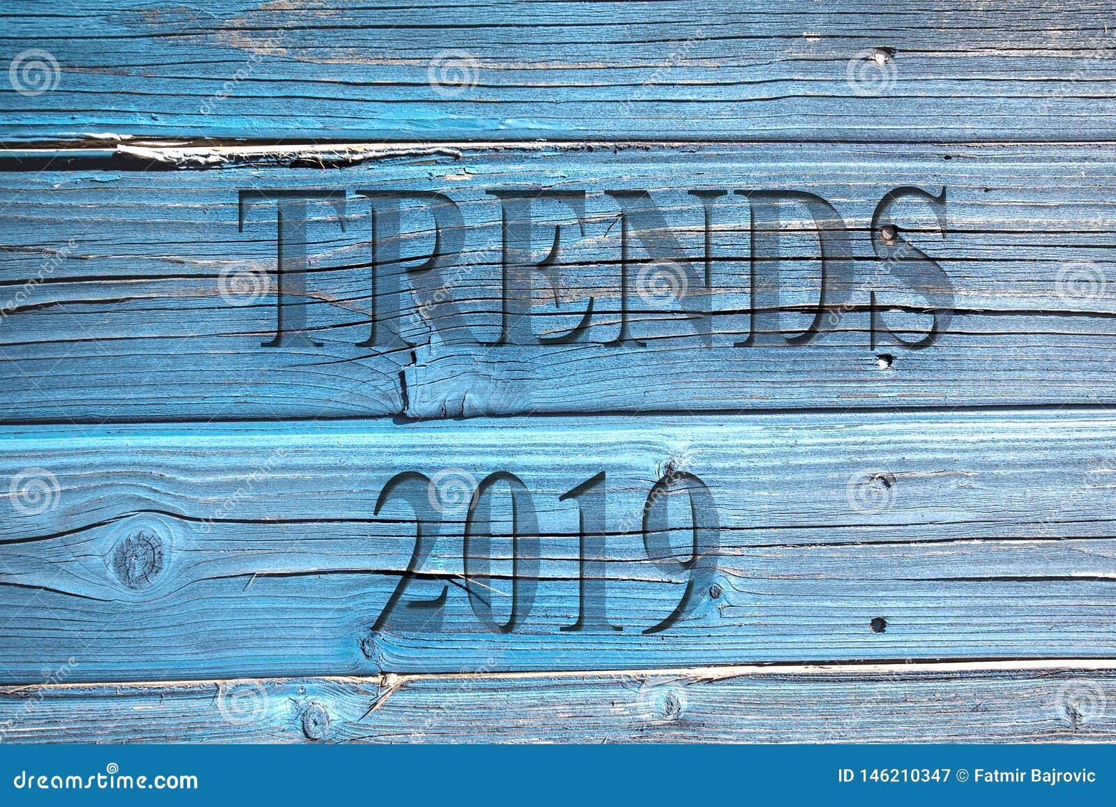 Οι τάσεις και ο αριθμός 2019 λέξης σε μια ξύλινη μπλε επιφάνεια
