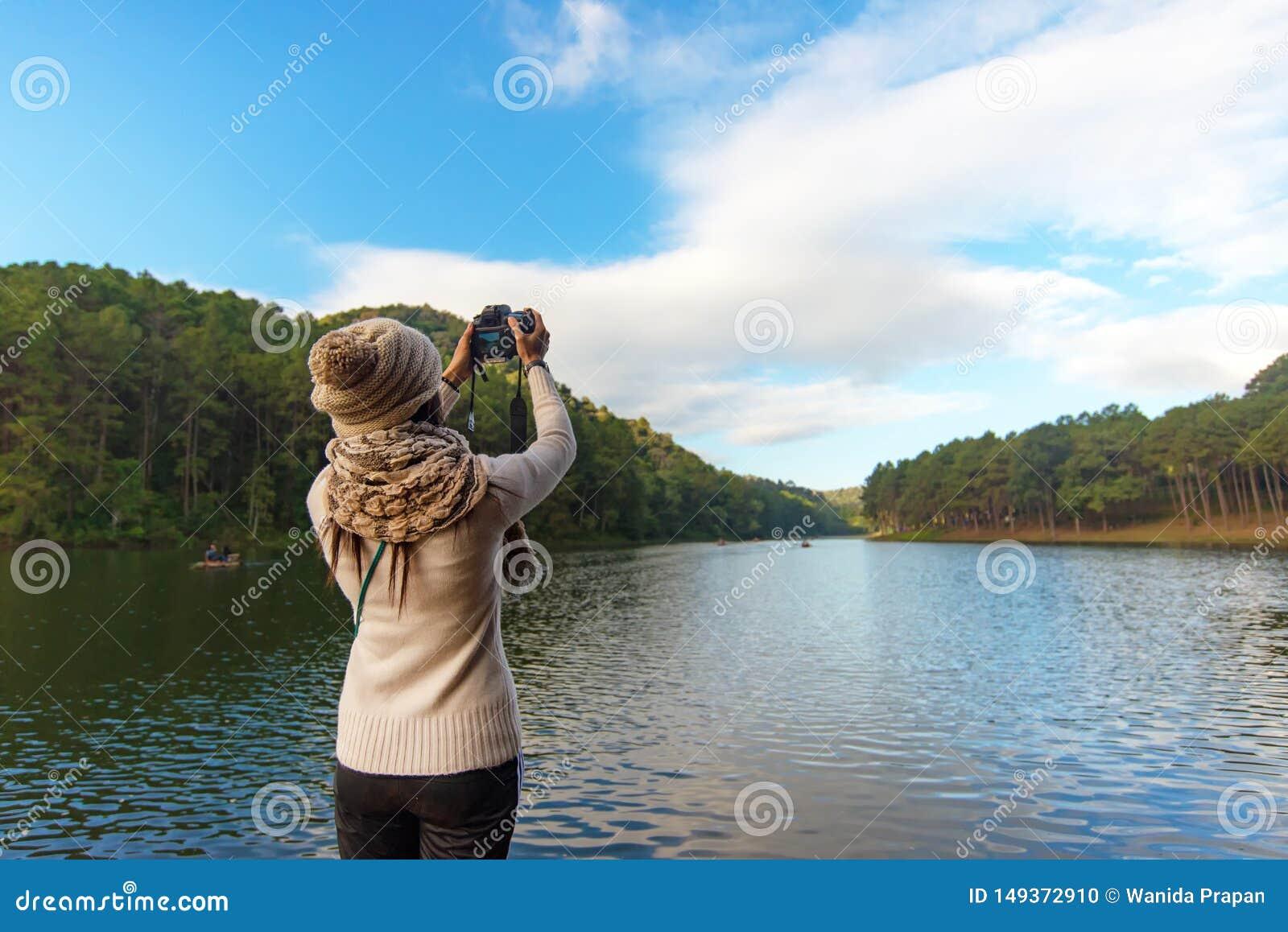 Οι ταξιδιωτικές γυναίκες που το ευτυχές αγαθό ελευθερίας αισθήματος χαλαρώνει και παίρνει μια φωτογραφία στο πεζούλι στο θέρετρο