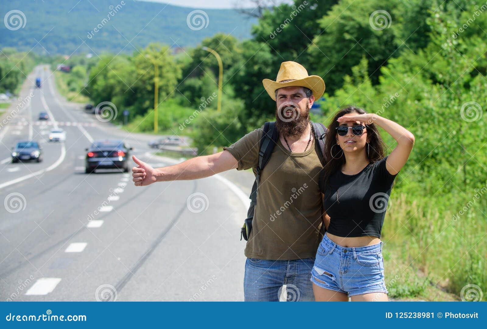 Οι ταξιδιώτες προσπαθούν να σταματήσουν το αυτοκίνητο Να κάνει ωτοστόπ είναι ένας από τους φτηνότερους τρόπους Hitchhikers ζεύγου