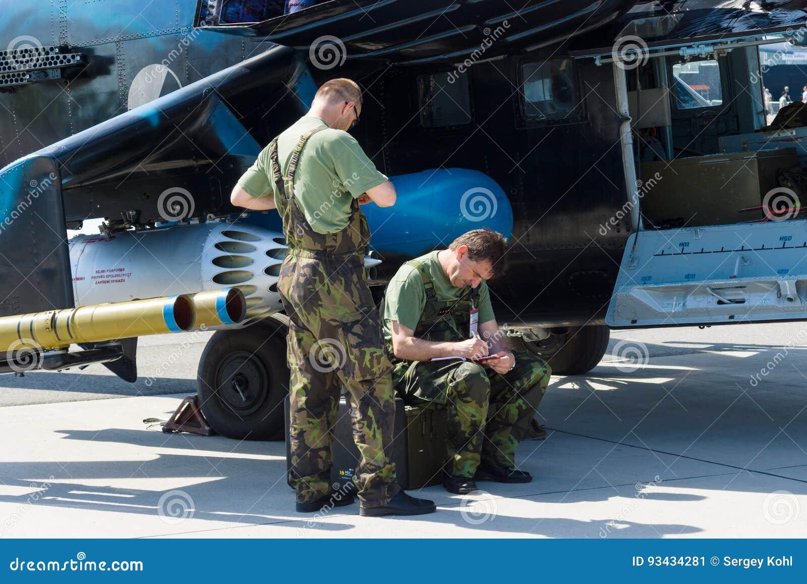Οι τεχνικοί επιθεωρούν το επιθετικό ελικόπτερο με τις ικανότητες Mil mi-24 μεταφορών οπίσθιες