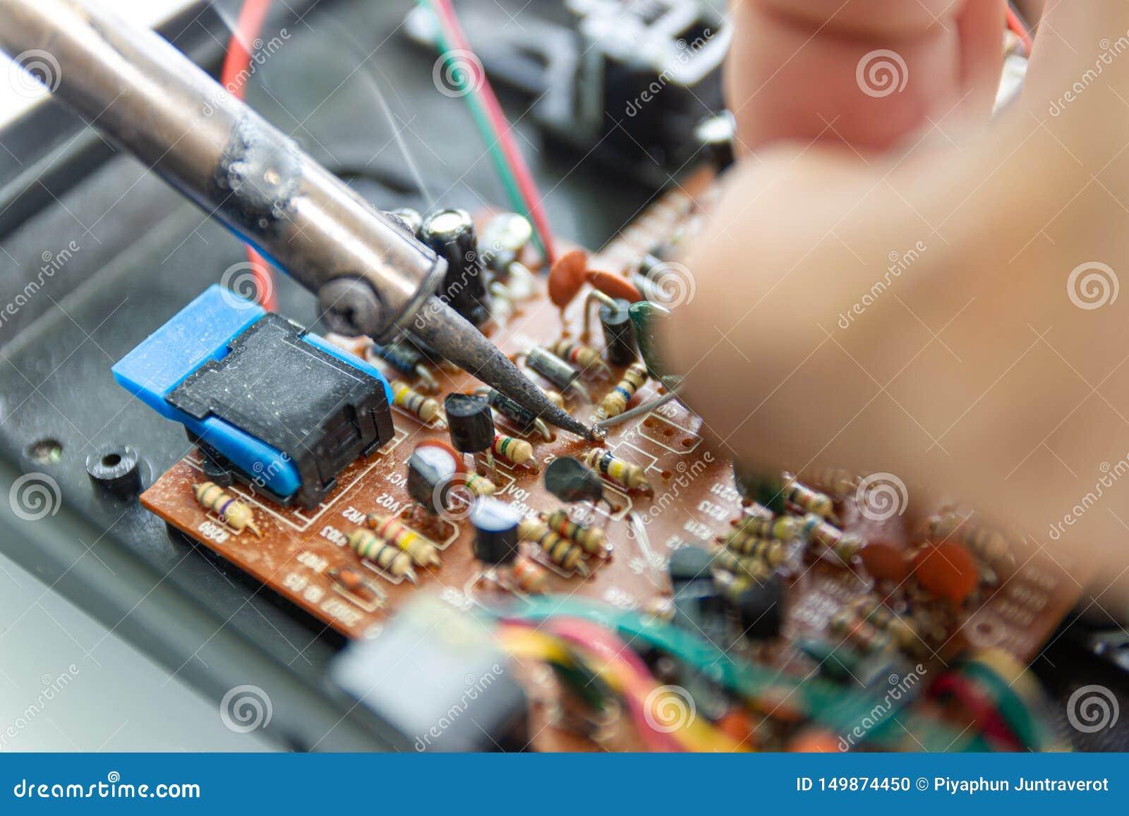 Οι τεχνικοί χρησιμοποιούν έναν συγκολλώντας σίδηρο για την επισκευή ηλεκτρονική
