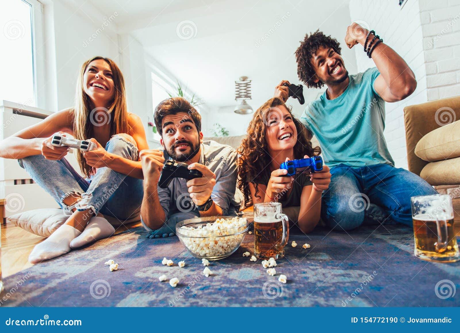 Οι φίλοι παίζουν τα τηλεοπτικά παιχνίδια μαζί στο σπίτι, που έχουν τη διασκέδαση