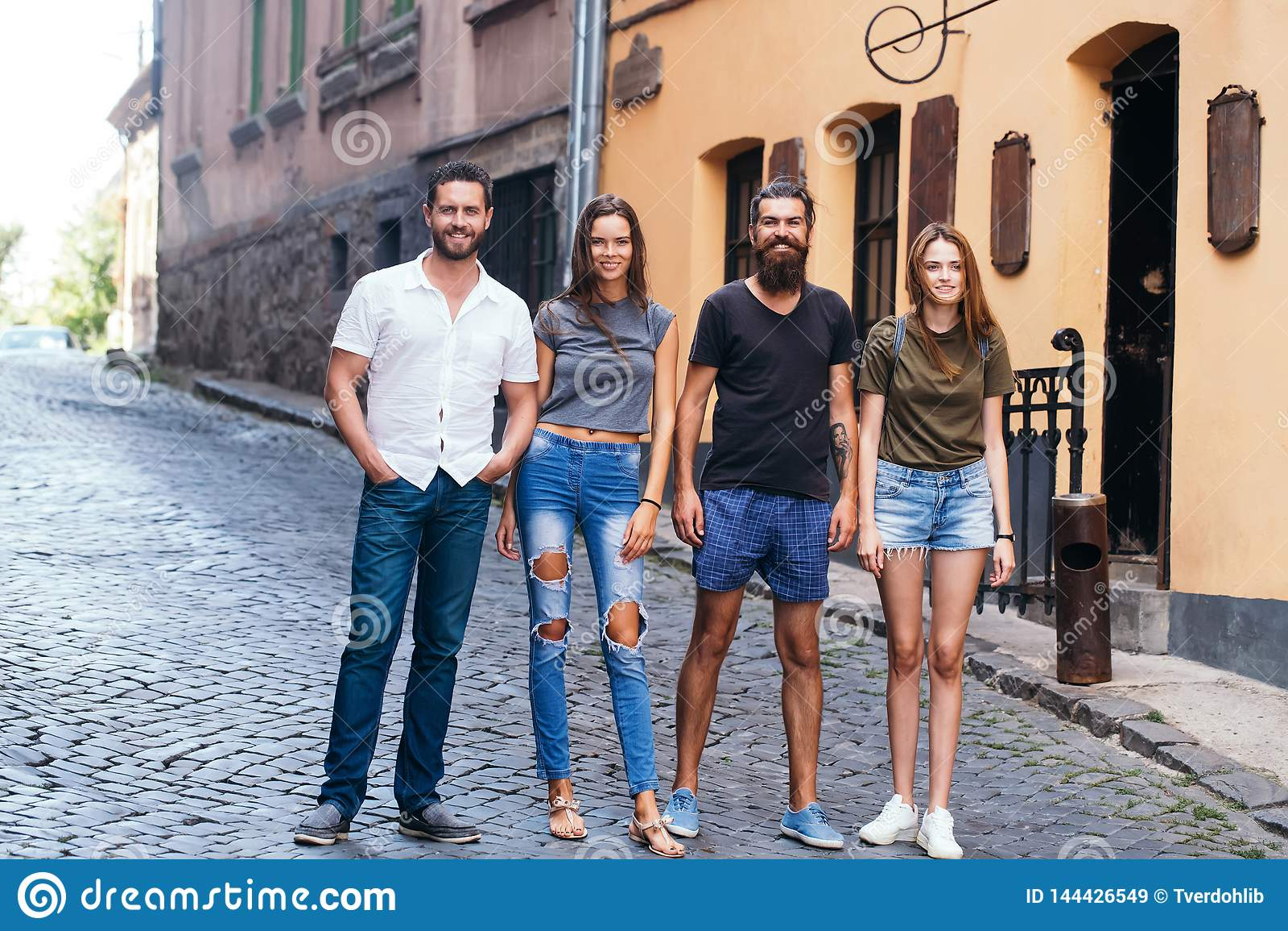 Οι φίλοι χαμογελούν στην οδό πόλεων, αστικό ύφος