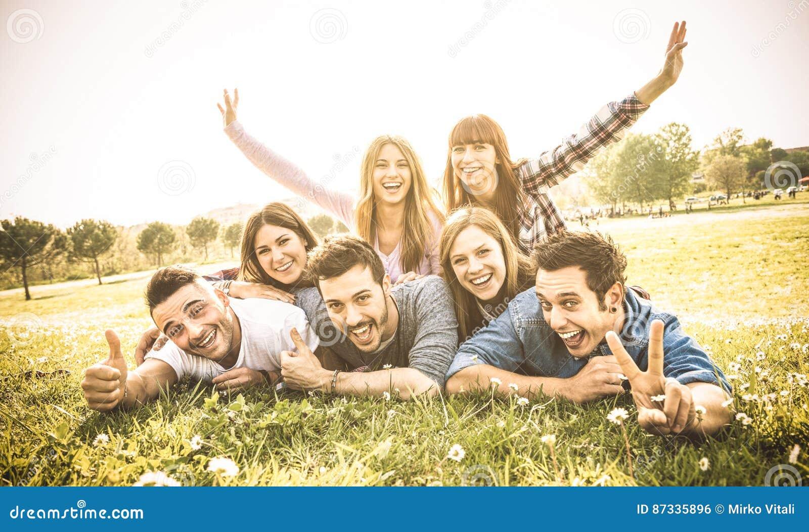 Οι φίλοι ομαδοποιούν την κατοχή της διασκέδασης μαζί με την αυτοπροσωπογραφία στο λιβάδι