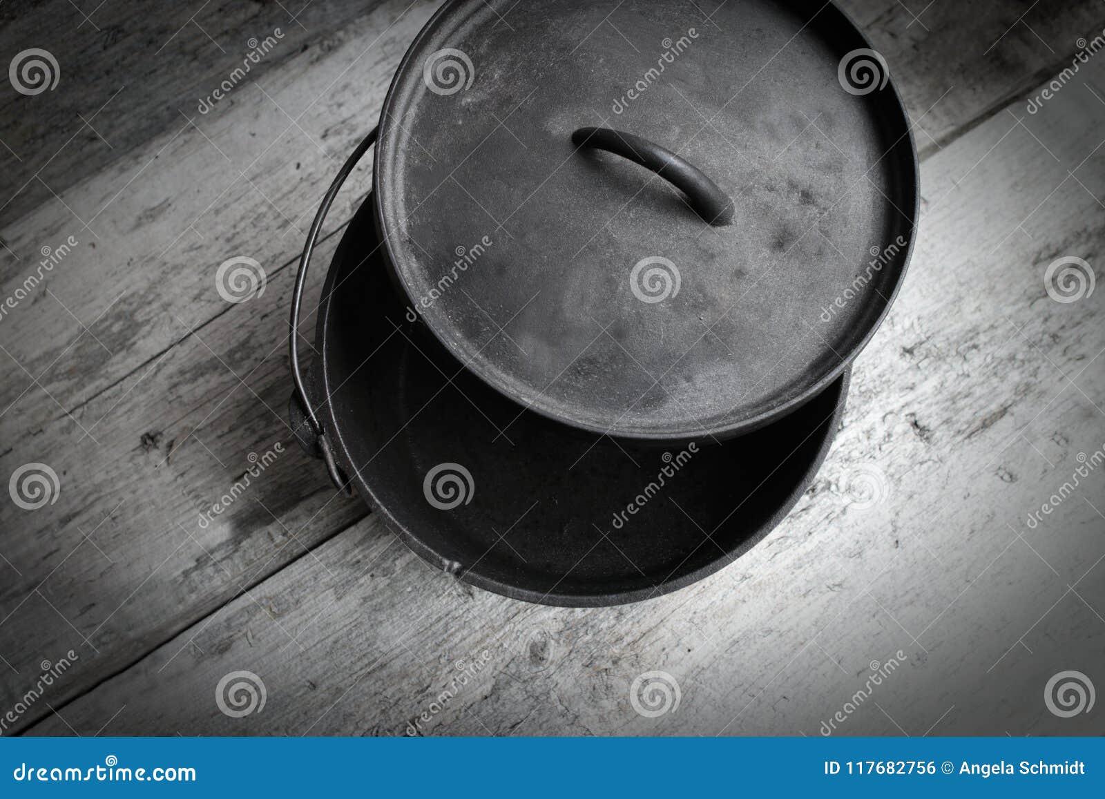Ολλανδικός φούρνος χυτοσιδήρου κατά το ήμισυ ανοικτός στο ξύλινο υπόβαθρο