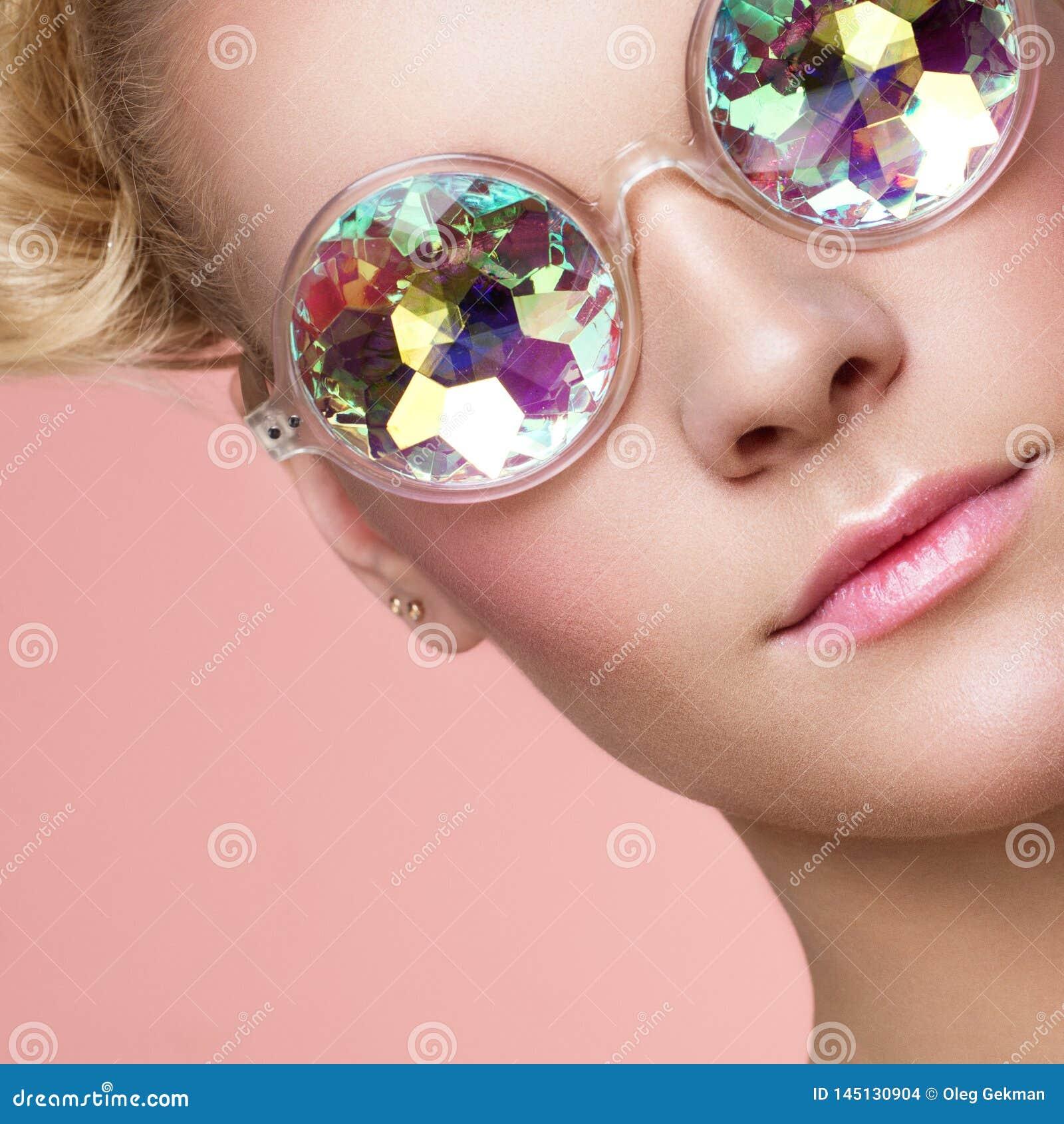 Πορτρέτο της όμορφης νέας γυναίκας με τα χρωματισμένα γυαλιά