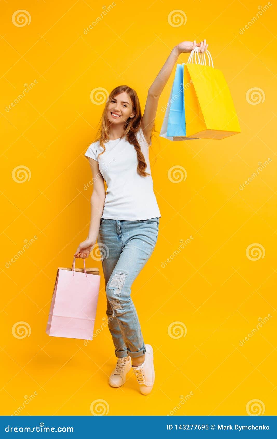 Ολόκληρο πορτρέτο μιας νέας όμορφης γυναίκας, με τις πολύχρωμες τσάντες, σε ένα κίτρινο υπόβαθρο