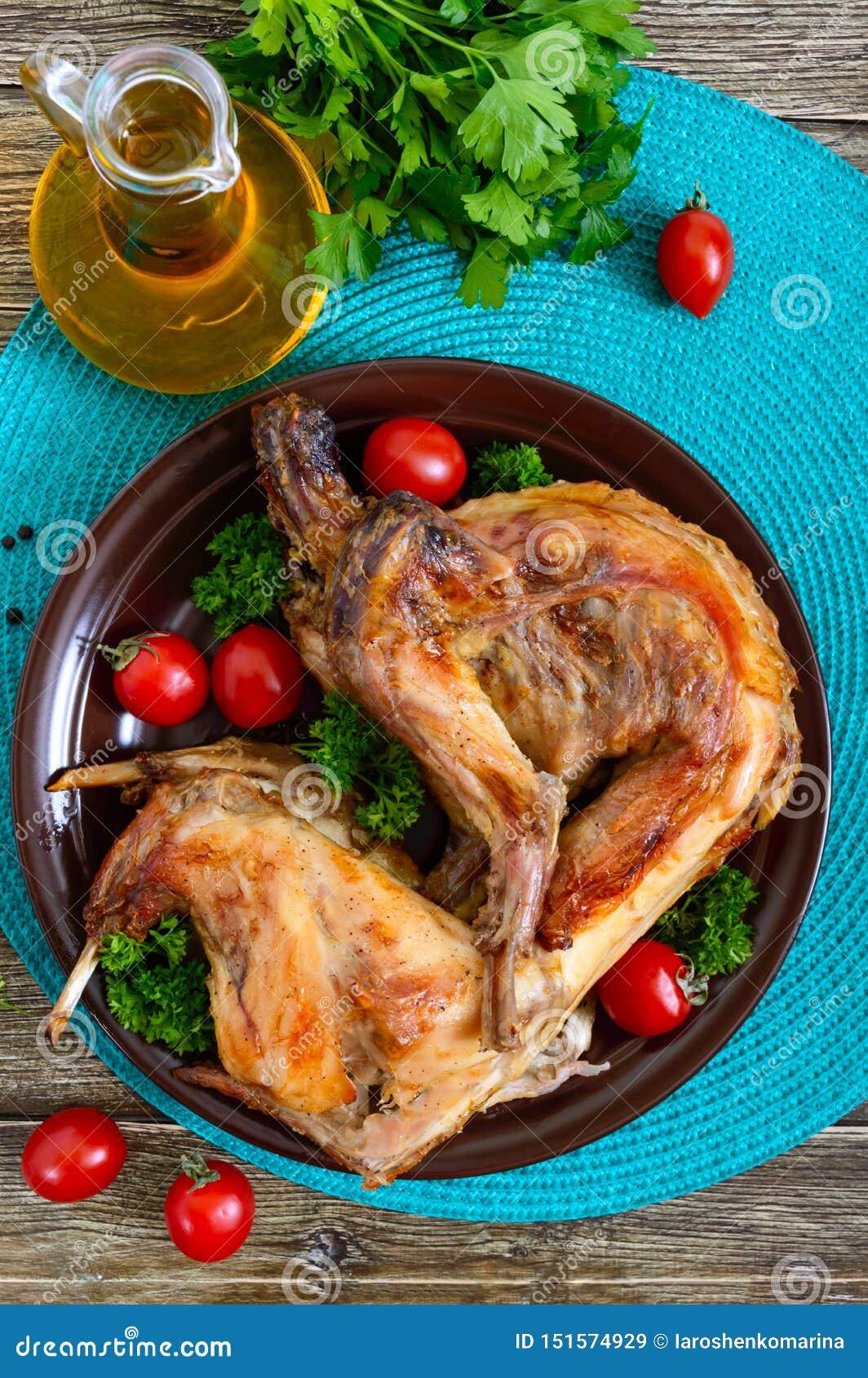 Ολόκληρο ψημένο κουνέλι με τα πράσινα και ντομάτες σε ένα πιάτο Νόστιμο διαιτητικό κρέας