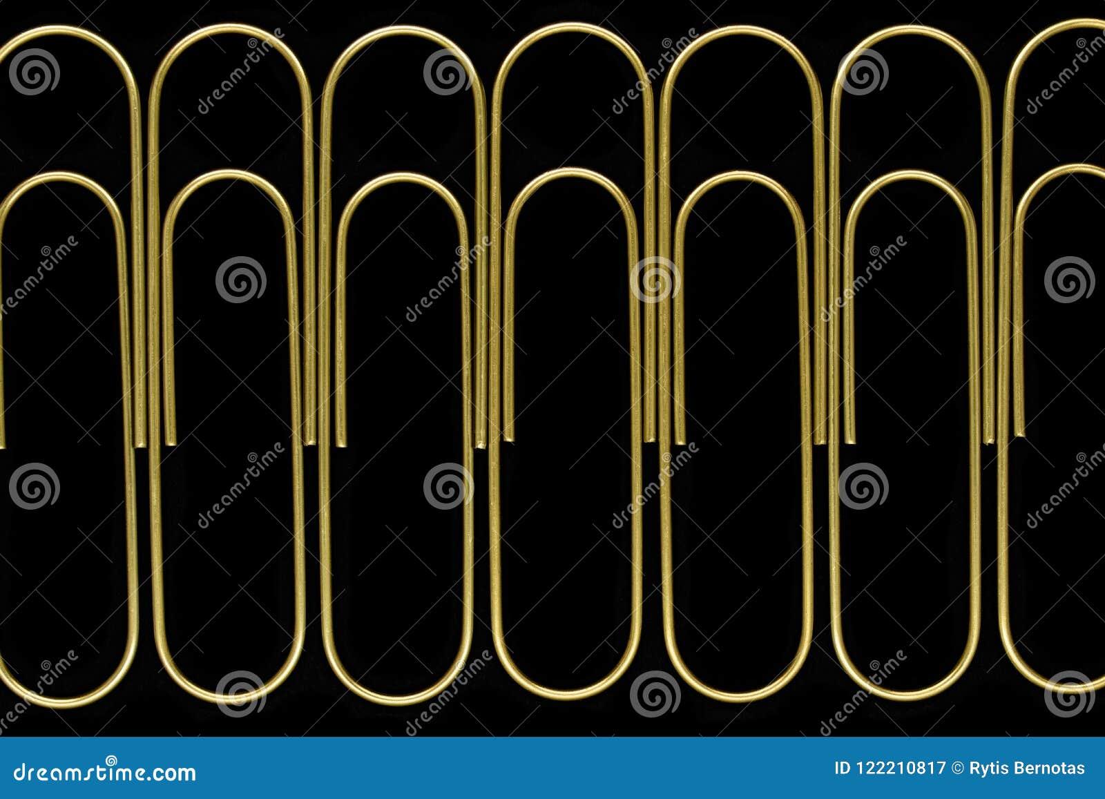 Ομάδα αιχμηρής και σαφούς άποψης των χρυσών paperclips που στέκονται στη γραμμή στη μαύρη επιφάνεια υποβάθρου