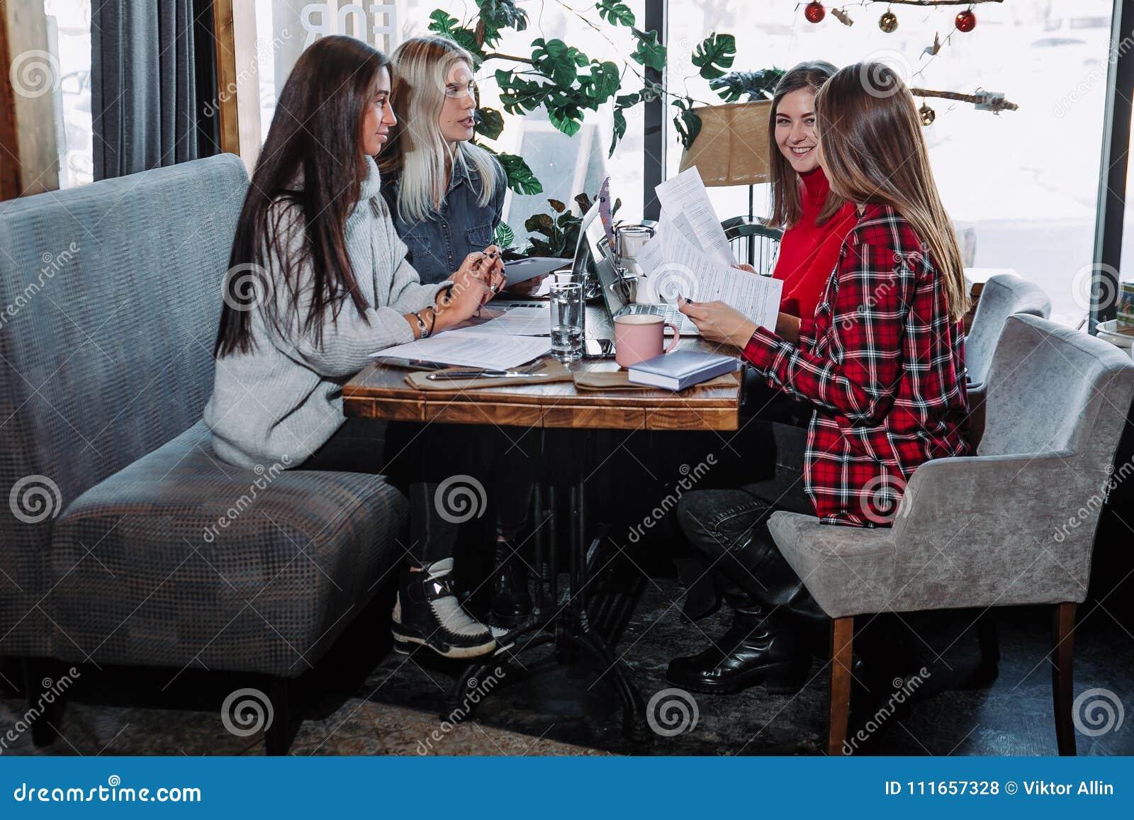 Ομάδα ανθρώπων που εργάζεται στο επιχειρησιακό πρόγραμμα στον καφέ, που κάθεται στον πίνακα με τα φύλλα του εγγράφου και του lap-