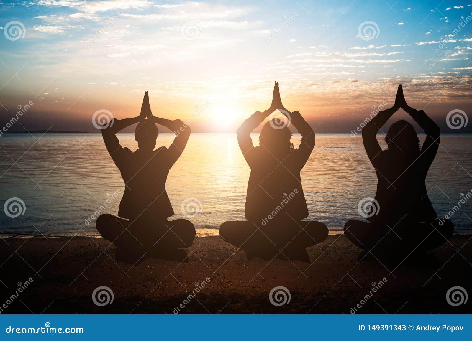 Ομάδα ανθρώπων Meditating στην παραλία