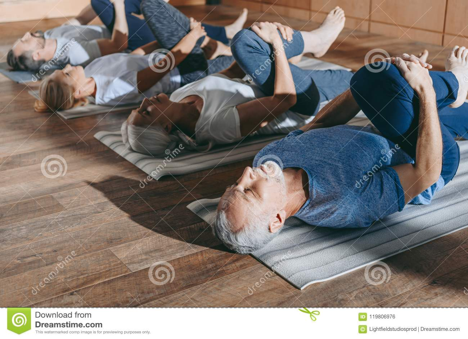ομάδα ανώτερων ανθρώπων που τεντώνει στα χαλιά γιόγκας