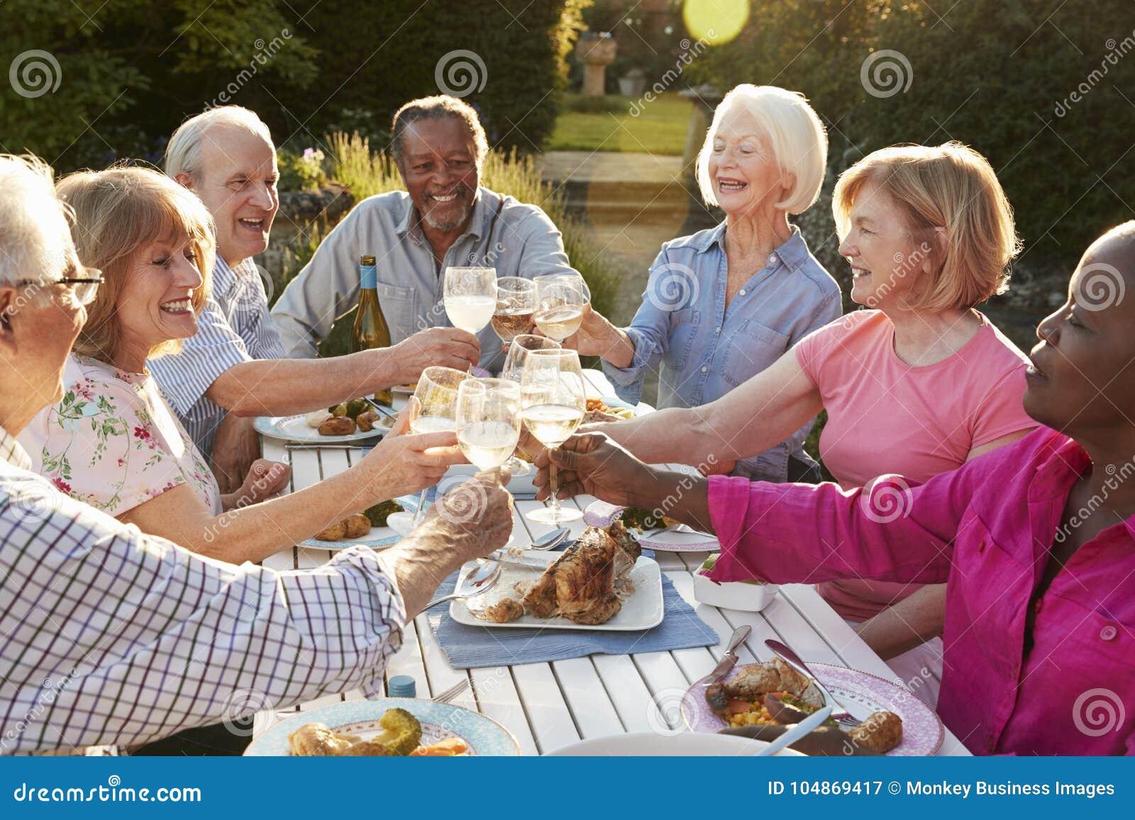 Ομάδα ανώτερων φίλων που κατασκευάζουν μια φρυγανιά στο υπαίθριο κόμμα γευμάτων