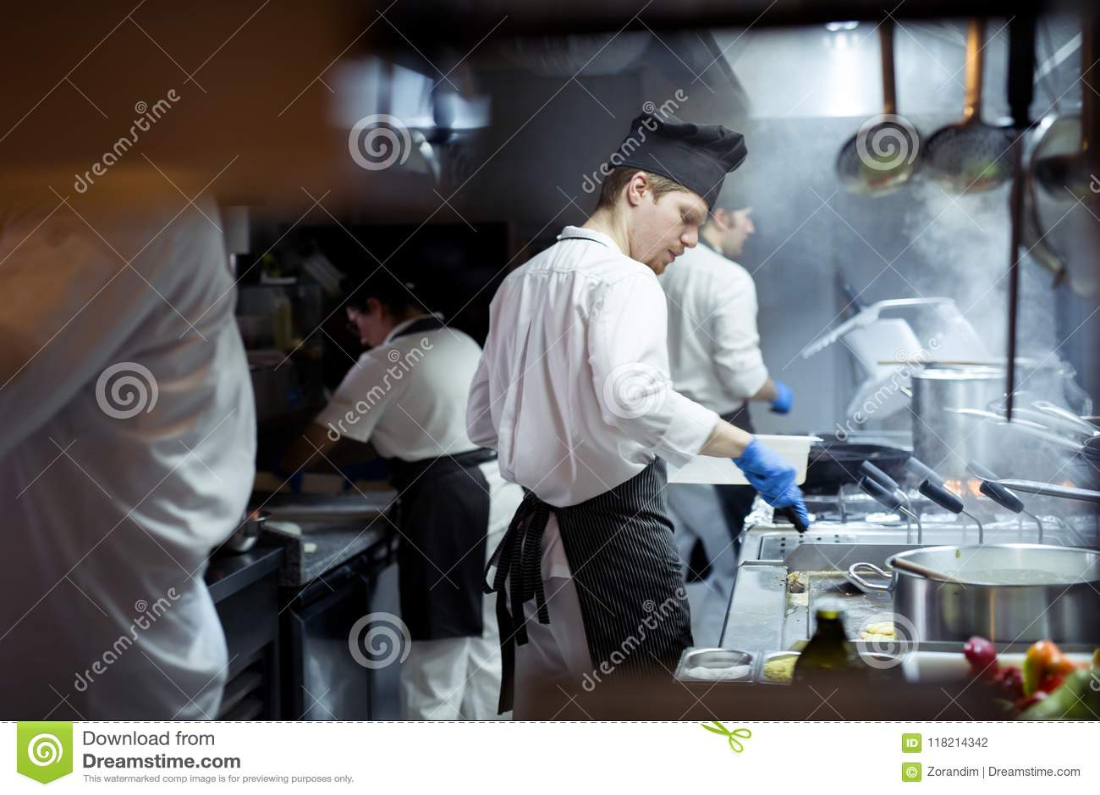 Ομάδα αρχιμάγειρα που προετοιμάζει τα τρόφιμα στην κουζίνα ενός εστιατορίου
