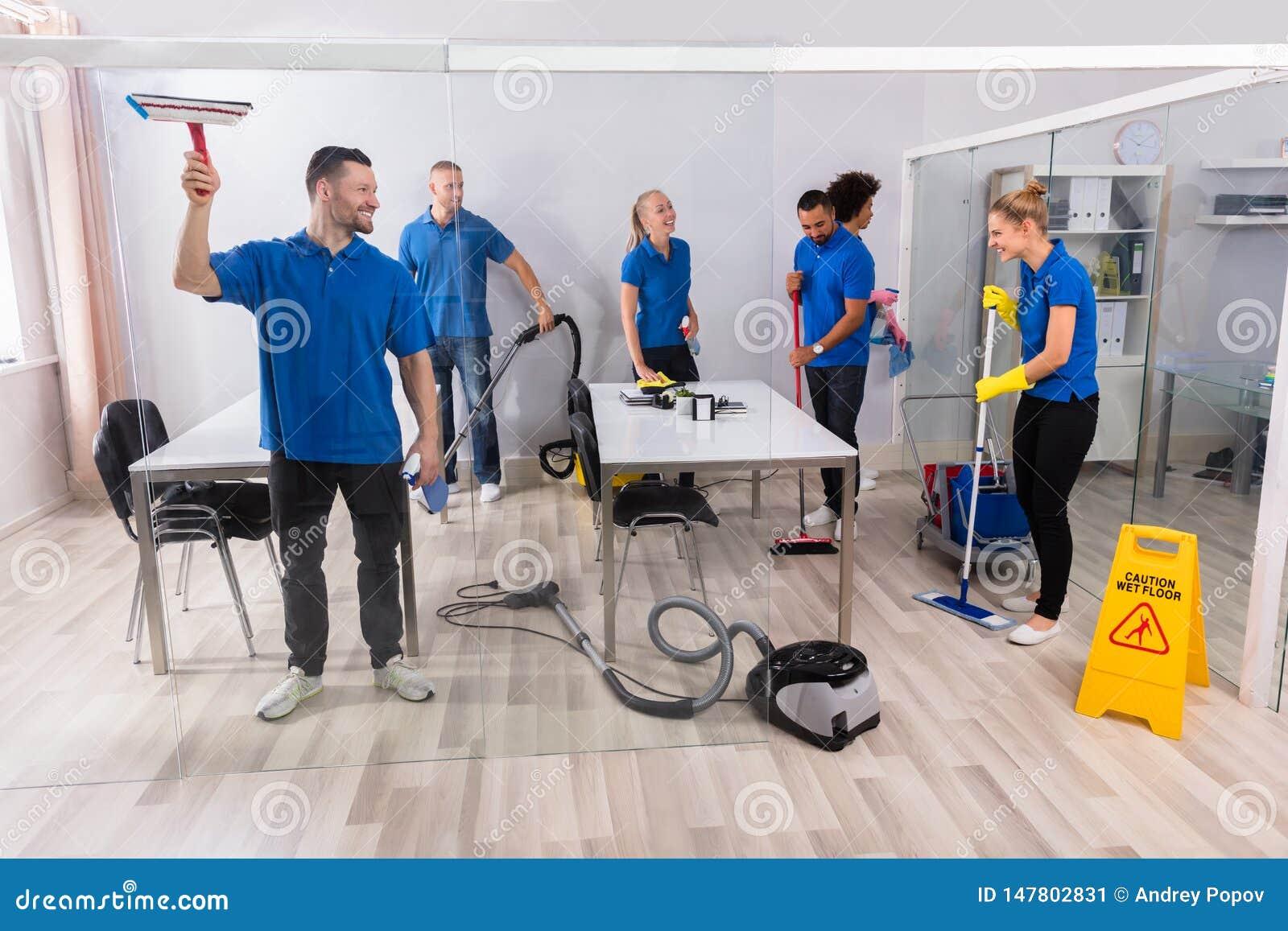 Ομάδα ειδικευμένα Janitors που καθαρίζουν το γραφείο
